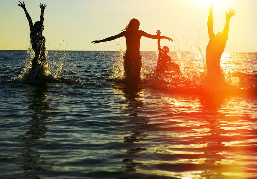 24178264 - silhouettes of young group of people jumping in ocean at sunset